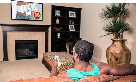 Мужчина просматривает телевизор с рекламой тренажера для сжигания жира фото